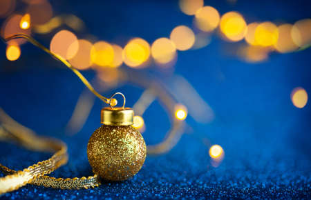 Christmas or New Year festive background with Christmas gold baubles on glitter blue backdrop. Festive winter concept with copy space.