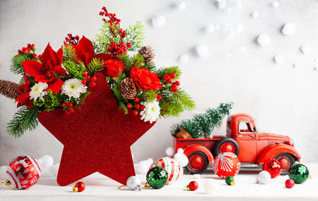 Festive winter flower arrangement in vase of red star shape and Christmas baubles on table. Christmas flower composition for holiday. 免版税图像
