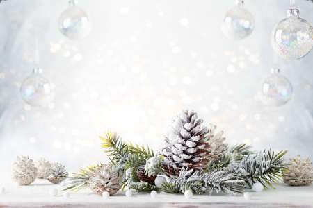 Christmas still life with snowy pine cones, baubles and fir branches on light background. Winter or Christmas festive concept.
