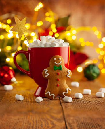 Christmas homemade gingerbread cookie and cup of hot chocolate with marshmallow on wooden table. Christmas food and drink concept 免版税图像