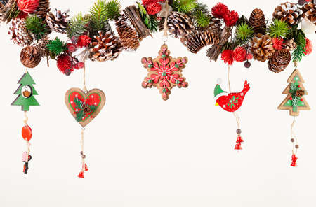 Christmas or New Year decor with hanging garland of fir branches, red berries, pine cones and other wooden ornaments. Winter festive concept 免版税图像