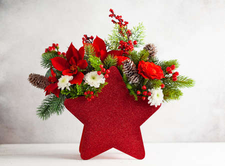 Festive winter flower arrangement in vase of red star shape. Christmas flower composition for holiday.