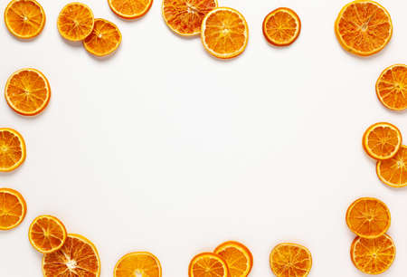 Christmas composition with dried oranges slices on white background. Natural dry food ingredient for cooking or Christmas decor for home. Flat lay, copy space.