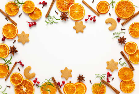 Christmas composition with cookies, dried oranges, cinnamon sticks and herbs on white background. Natural food ingredient for cooking or Christmas decor for home. Flat lay, copy space.