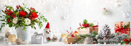 Christmas or New Year concept with flower arrangement, gift boxes and Christmas decorations on table. Festive still life. 免版税图像