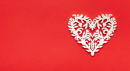 Festive composition with openwork white heart on red