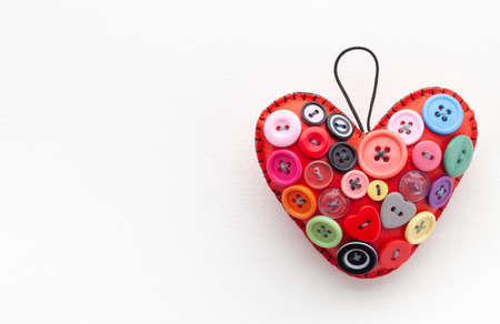 Valentine's Day concept with red heart and assorted buttons.