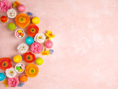 Easter eggs and colorful spring flowers on pastel pink background. Minimal holiday concept with copy space for text. Flat lay pattern. Reklamní fotografie