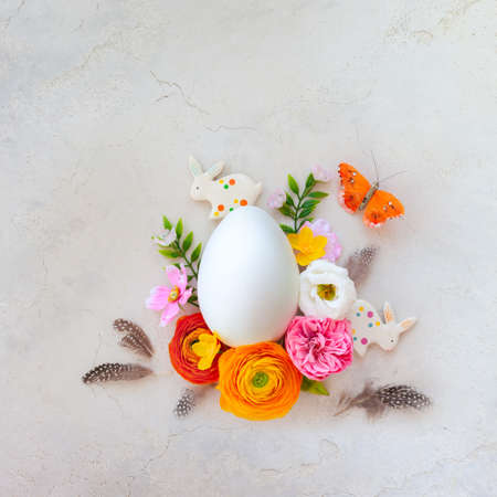 Creative Easter concept made of white egg, bunny, butterfly and spring flowers around on vintage background. Flat lay.
