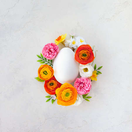 Creative Easter concept made of white egg and spring flowers around on vintage background. Flat lay.