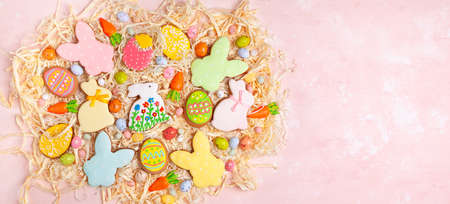 Colorful Easter homemade gingerbread cookies in shape of eggs and bunny and candy. Easter baking concept. Top view.