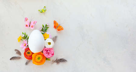 Creative Easter concept made of white egg, butterfly and spring flowers around on vintage background. Flat lay.