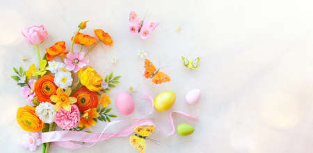 Holiday concept with bouquet of spring flowers, Easter eggs and butterfly on pastel vintage background. Easter composition, flat lay.