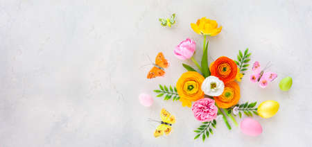 Holiday concept with spring flowers, Easter eggs and butterfly on pastel vintage background. Easter concept