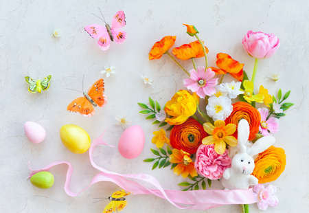 Holiday concept with bouquet of spring flowers, Easter eggs, bunny and butterfly on pastel vintage background. Easter composition, flat lay.