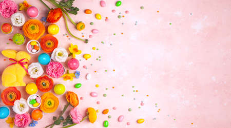 Easter eggs, Bunny, candy and colorful spring flowers on pastel pink background. Minimal holiday concept with copy space for text. Flat lay pattern.