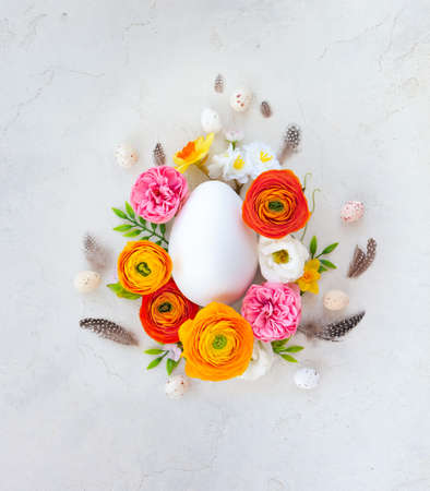 Creative Easter concept made of eggs, feathers and spring flowers around on vintage background. Flat lay.