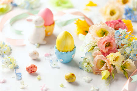 Happy Easter background with colorful eggs, candy and bunch of flowers. Table decorating for holiday.