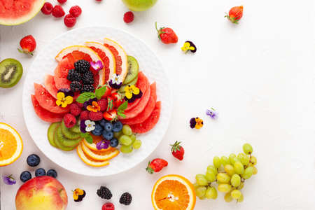 Delicious healthy salad of fresh fruits, berries and edible flowers on white plate. Clean eating. Top view. Banco de Imagens