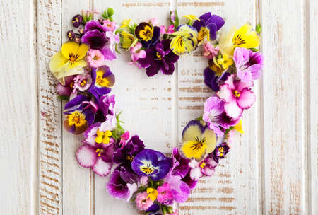 Heart of beautiful fresh flowers on old wooden background
