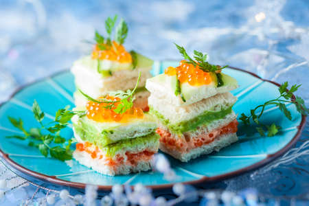 Striped sandwiches with red caviar, cucumber and avocado for holiday 免版税图像