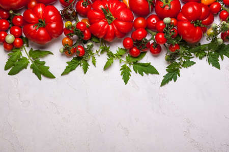 Various fresh tomatoes with green leaves. Top view