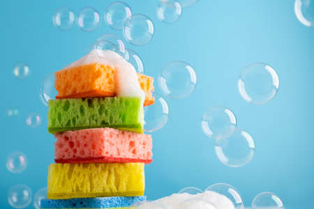 Household Cleaning Scrub Colored Sponges with soap foam and bubbles. Kitchen Dishwashing Sponge on blue background. Cleaning home concept. Space for text. 免版税图像