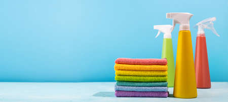 Colored supplies for cleaning on blue background. Spray Bottles of detergent and rags rainbow colors. Concept of spring cleaning home.