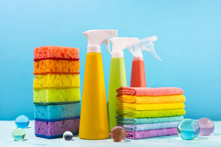 Colored supplies for cleaning on blue background. Spray Bottles of detergent, sponges and rags rainbow colors. Concept of spring cleaning home.