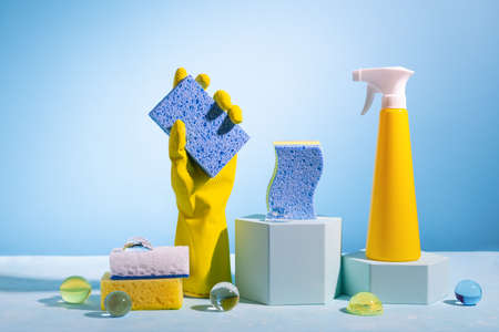 Creative still life with supplies for cleaning or housekeeping on podiums over blue background. Female hand in yellow rubber glove with clean sponge, spray bottle and color sponges.