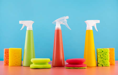 Concept of spring cleaning home. Colored supplies for cleaning on blue background.Bottles of detergent and sponges.