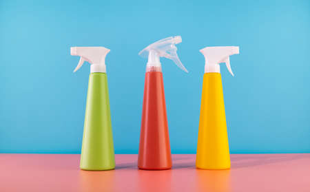 Cleaning Spray Bottles of detergent and bubbles soap.Concept of spring cleaning home. Colored supplies for cleaning on blue background. 免版税图像