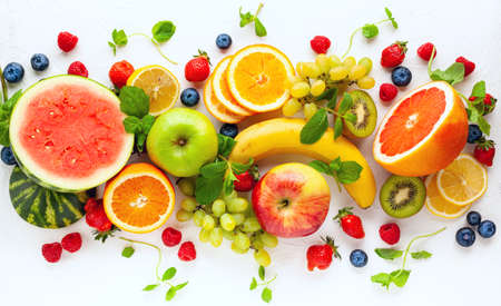 Assorted fresh fruits and berries on white background. Clean eating, healthy life. Top view.