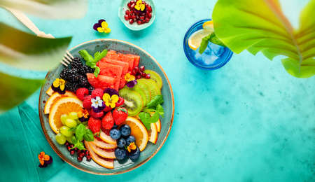 Delicious healthy salad of fresh fruits, berries and edible flowers on plate. Clean eating. Top view. 免版税图像