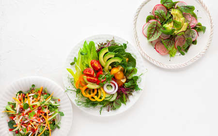 Various healthy salads of fresh vegetables, fruits and microgreens on table. Clean eating, lunch bowl. Top view. Concept taste of home meal.