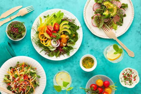 Various healthy salads of fresh vegetables, fruits and microgreens on table. 免版税图像