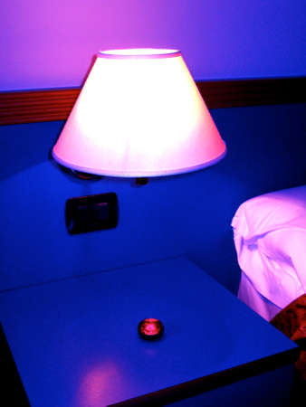 bedside lamps: bright red object on a bedside table