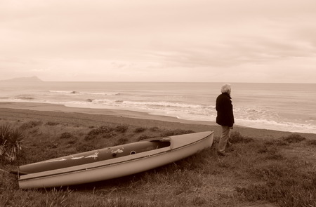 metaphysics: Abandoned boat on the sand with a man looking at the horizon