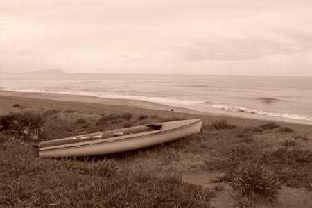 melancholia: Abandoned boat on the sand facing the sea
