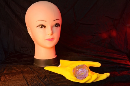 head dummy and yellow rubber glove with crystal stone