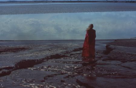 Donna con mantello in un deserto con miraggio Archivio Fotografico - 86363254
