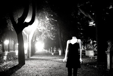 Mannequin in avenue of statues of a garden at night Stock Photo