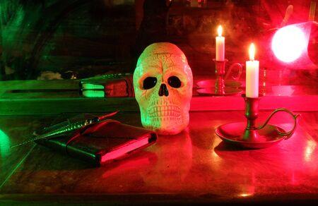 Cranio e candela accesi con il vecchio taccuino e il pennello antico Archivio Fotografico - 87844746