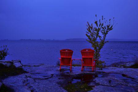 Sedie rosse sul lago Archivio Fotografico - 90000514