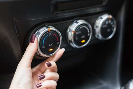 Woman turning on car air conditioning system switch Stock Photo