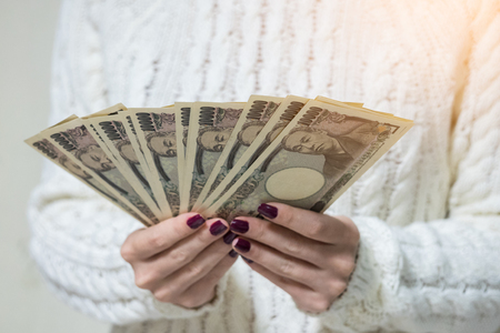 Womans hand recount bundle of japanese money banknote
