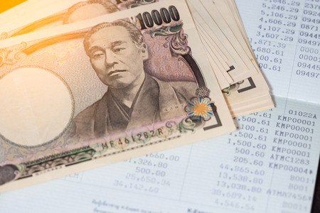 Business, finance, investment or accounting concept : Japanese money banknoter and saving account book or financial statement
