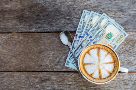 Top view of coffee cup on dollar bills pile and wooden table. Business concept.