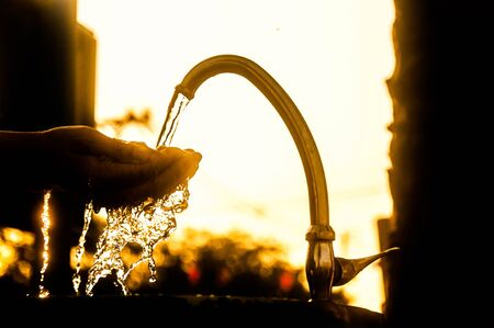 Woman washing her hands at the tap,Water shortage concept,silhouette style