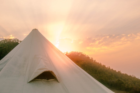 White tent with green mountain and sunset.
